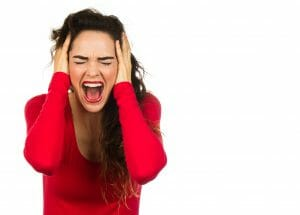 Woman holding her head screaming in frustration