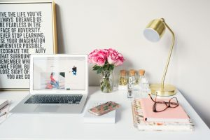 Clean and tidy desk with macbook brass lamp and notebooks