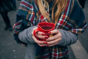 woman cupping her hands around a hot drink to stay warm